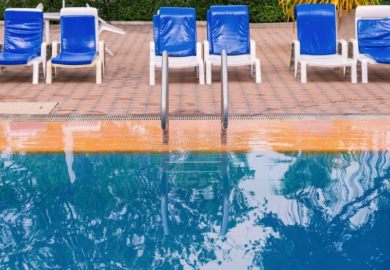 Luksusowy pływacki basen z białymi deckchairs obrazy stock