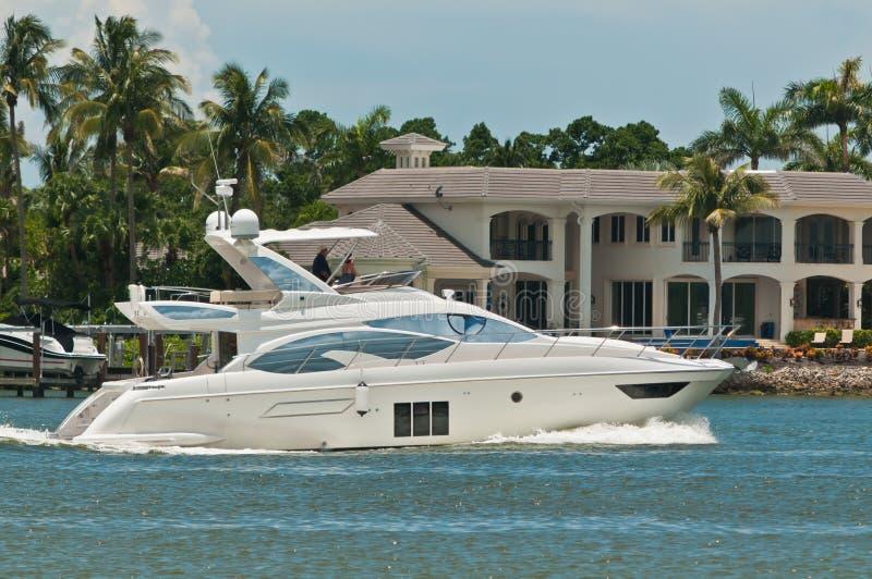 Luksusowy powerboat pływa statkiem tropikalnego kanał i kondominia obraz stock