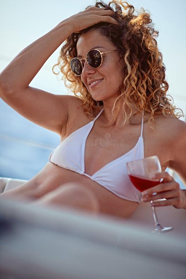 Luksusu wakacje na dennej łodzi – kobieta pije wino fotografia royalty free