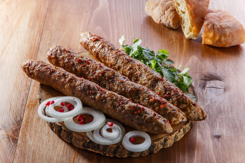 Lula kebab with herbs. On a wooden surface stock photography