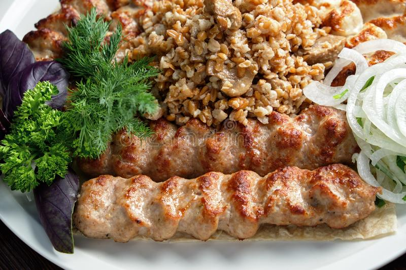 Meat dish lula kebab. Lula kebab meat dish with vegetable side dish in a beautiful serving on a white plate. restaurant menu royalty free stock photography
