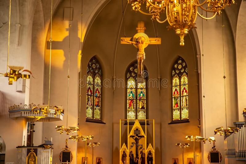 Lulea, Sweden - July 05, 2019: Catholic Cathedral in sunlight, statue of Jesus on cross sunset royalty free stock image
