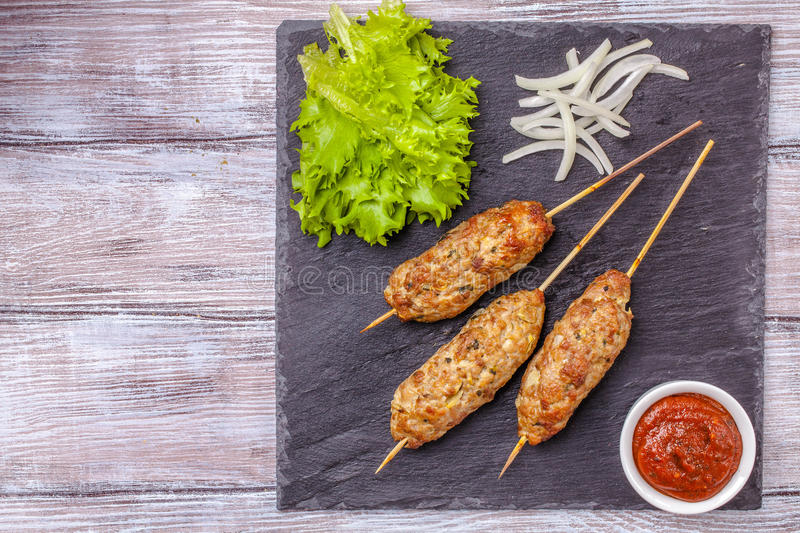 Lulya-kebab. Shish kebab on a stick, minced meat. Traditional Caucasian dish. With green salad, ketchup, spices. stock image
