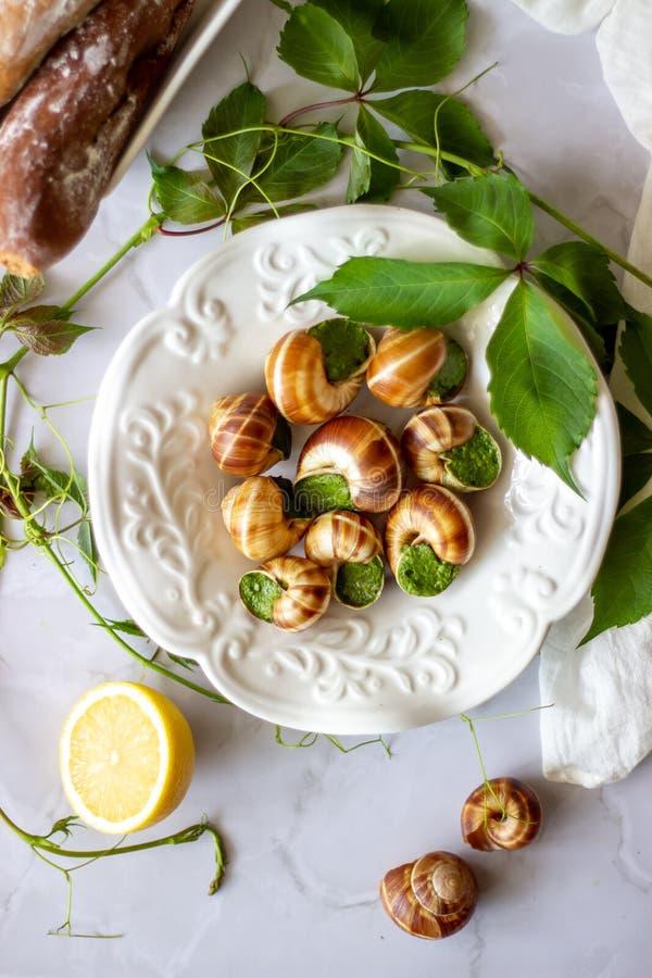 Lumaca di Bourguignonne con il limone Fondo di marmo Cucina francese fotografia stock