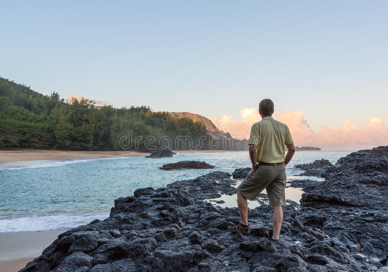 Lumahai Beach Kauai at dawn with man. Senior caucasian man overlooks the rocks and ocean at Lumahai Beach in Kauai in Hawaiian islands stock photo