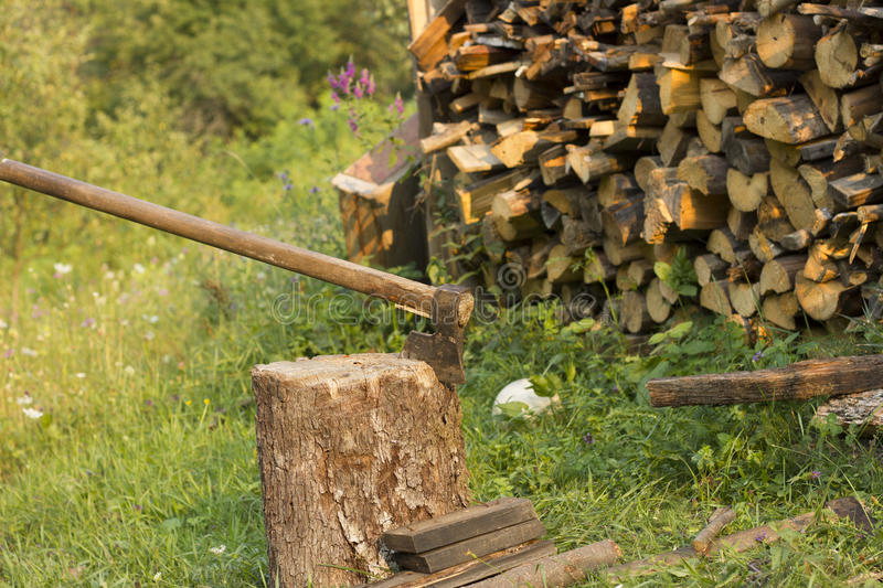 Chopping firewood. An axe on a chopping block with a stack of firewood stock photo