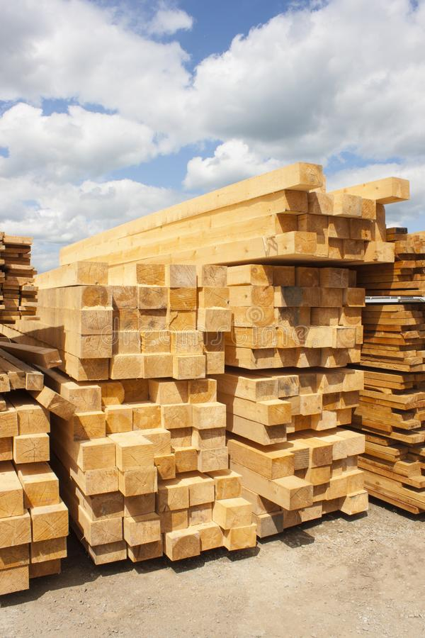 Lumber warehouse in the open air. Wooden beam, planks of wood, stacked in stacks. Sunny day, blue sky with clouds royalty free stock image
