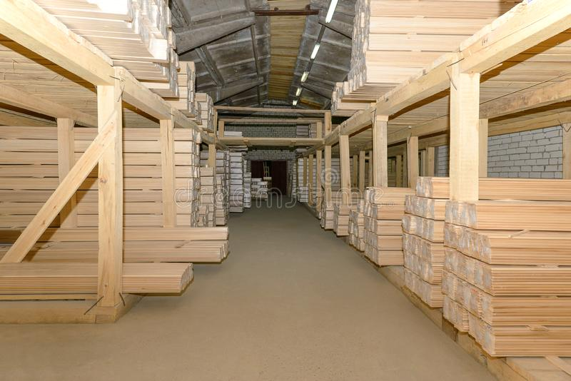 Lumber warehouse with shelves. Filled with linden lining stock photography