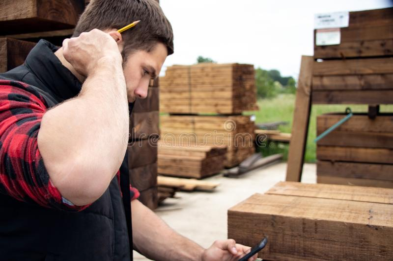Lumber yard worker, carpenter at wood yard counts inventory with mobile device. Storesman at small business lumber yard counts stock and records it with his stock photo