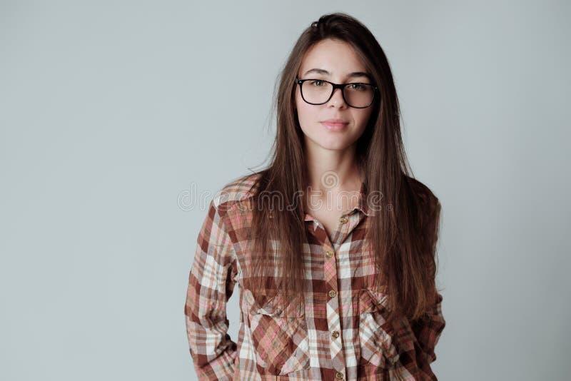 lumbercheck的自信逗人喜爱的年轻深色的女孩检查衬衣和玻璃 库存照片