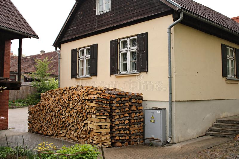 Lumbered chopped firewood for the winter and piled in stacks near the hut. Kuldiga, Latvia May 11, 2019.  stock photo