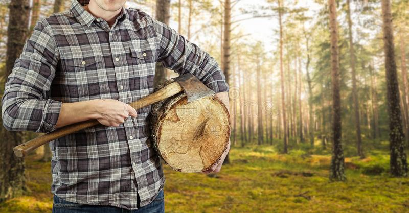 A lumberjack with an ax in his hand and a log. Logger with checkered shirt. Plenty of copy space for your own text or product stock images