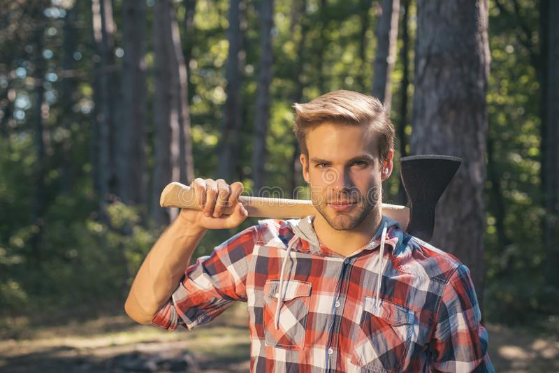 Lumberjack carries axe on shoulder. Deforestation. Handsome man with axe. Lumberjack in the woods with an ax. stock photo
