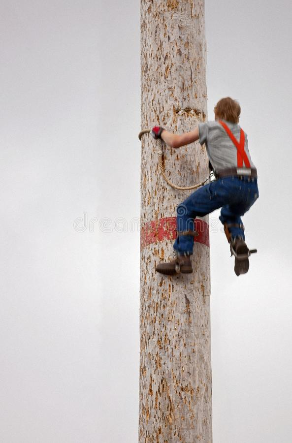 LUMBERJACK CLIMBING LARGE POLE WITH CLOUDY SKY IN BACKGROUND royalty free stock image