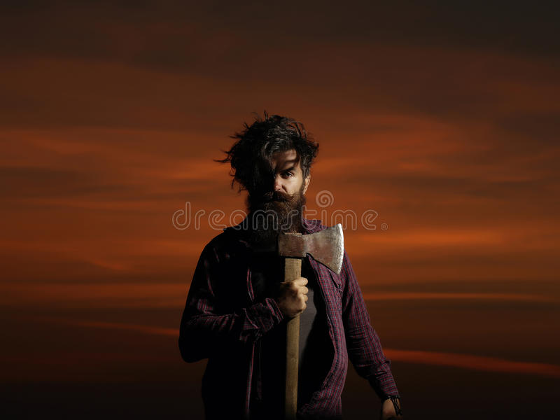 Lumberjack hipster on twilight. Strong man lumberjack hipster with long beard and moustache in checkered shirt with axe in hand on twilight on darkness royalty free stock photos