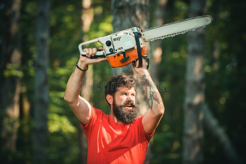 Lumberjack nel bosco con un'ascia di motosega Giovane uomo grazioso con un'ascia vicino alla foresta di Chainsaw Deforestazione L fotografia stock