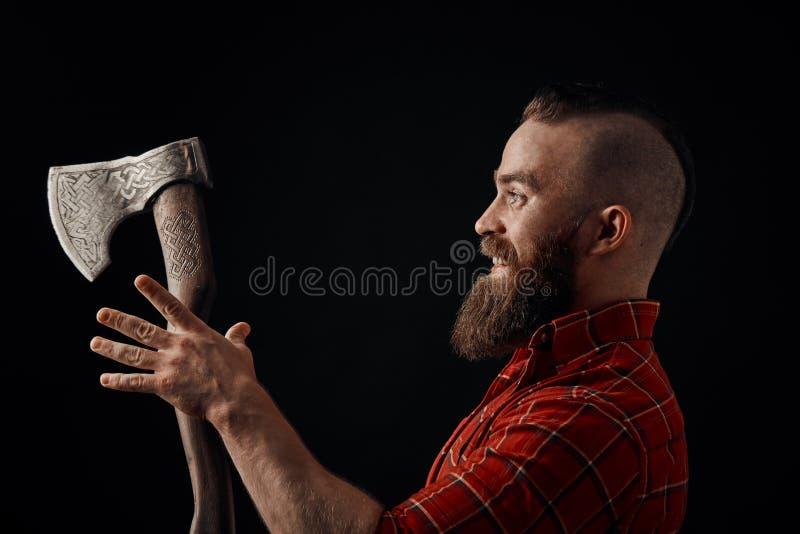 lumberjack Säker skäggig man som fästas till pannayxan arkivfoto