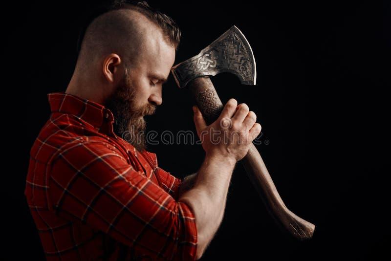 lumberjack Säker skäggig man som fästas till pannayxan arkivbild