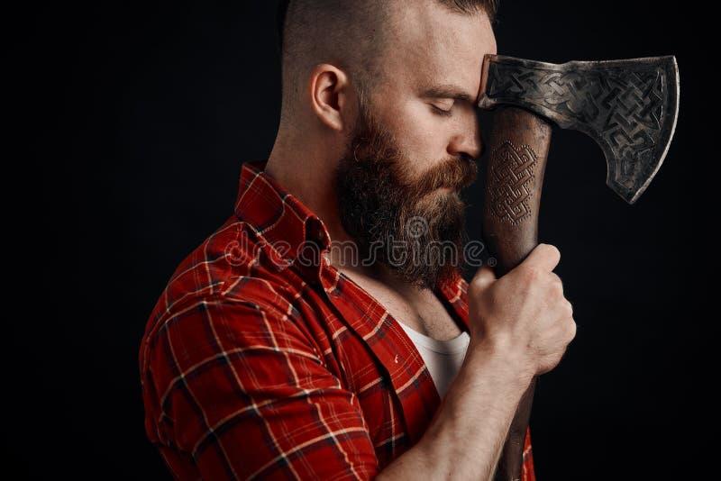 lumberjack Säker skäggig man som fästas till pannayxan royaltyfri bild