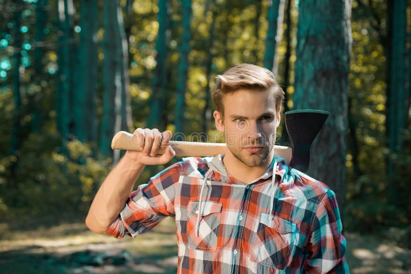 Lumberjack on serious face carries axe on shoulder. Bearded man with axe concept. Lumberjack with axe on forest stock photos