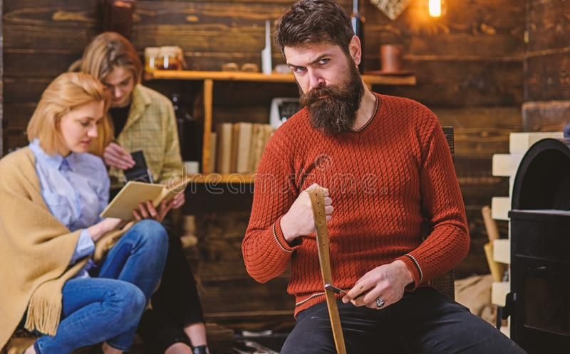 Lumberjack with strict look and long bushy beard whetting razor or knife, danger concept. Bearded man in retro outfit. Lumberjack with strict look and long bushy stock images