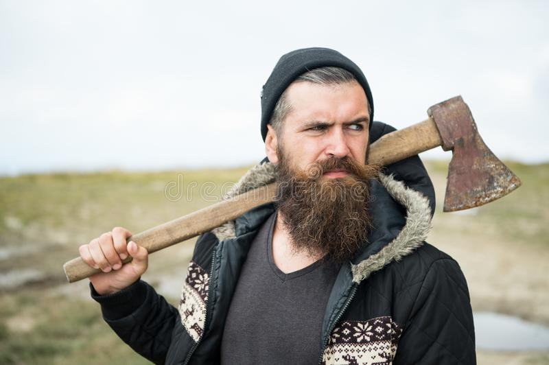 Lumberjack in the woods with an ax. Brutal bearded man with beard and moustache on winter day, snowy forest. Handsome man, hipster, lumberjack. Attractive royalty free stock images