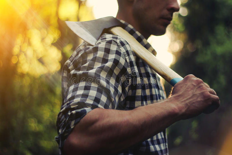 Lumberjack in the woods with an ax. Strong lumberjack is standing in the woods with an ax on his shoulder royalty free stock image