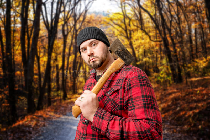 Lumberjack Woodsman In Forest Fall Foliage. A Lumberjack/Woodsman posing with his axe In a Forest during the Fall Season stock photo