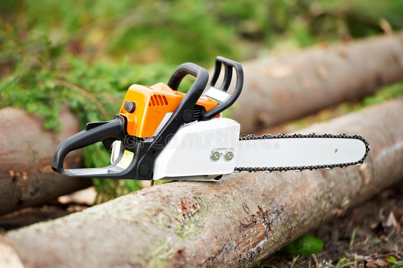 Lumberjack Work tool petrol Chainsaw. Lumberjack power Work tool petrol Chainsaw lying on log In The Forest stock images