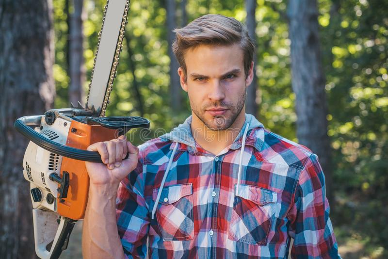 Lumberjack worker standing in the forest with chainsaw. Chainsaw. Stylish young man posing like lumberjack. Woodcutter royalty free stock photo