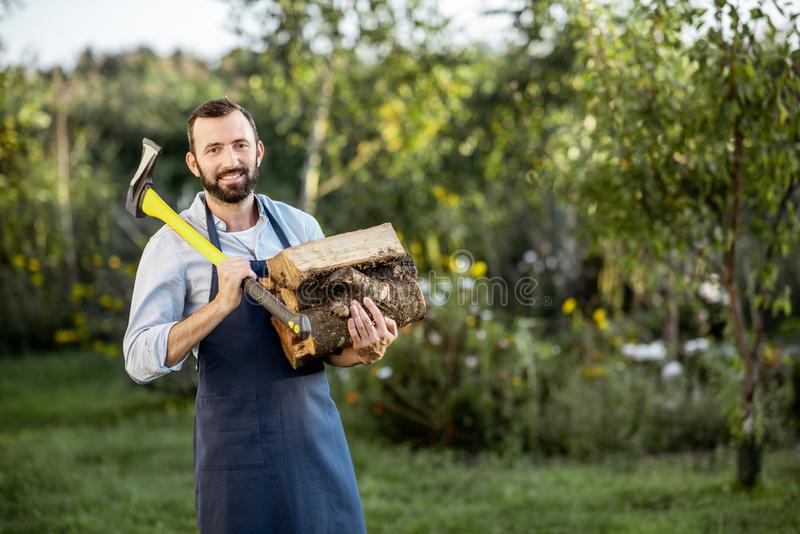 Lumberman with axe and wood outdoors stock image