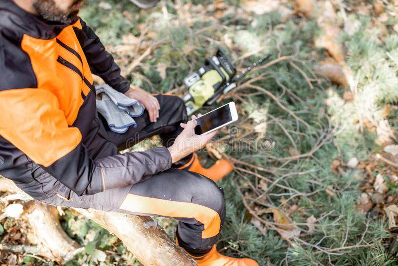 Professional lumberman resting with phone in the forest stock photo