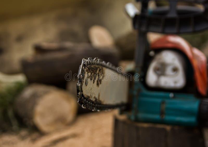 Lumberman using chainsaw sawing dry wood lying on ground. Lumberman using chainsaw sawing dry wood lying on ground stock image