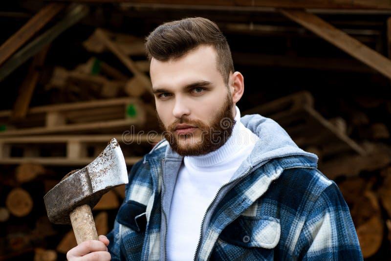 Lumbersexual begrepp Uppsökt rutig kläder för skogsarbetare bär yxan Skarpt blad Den brutala mannen samlar vedträ hipster arkivfoton