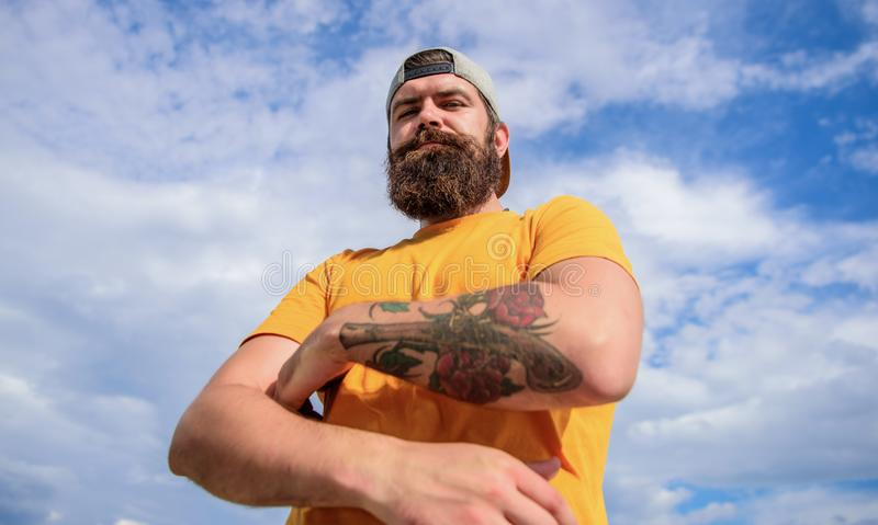 Lumbersexual tattooed well groomed hipster. Hipster with mustache and long beard. Too serious right now. Man bearded. Muscular brutal hipster outdoors sky stock images