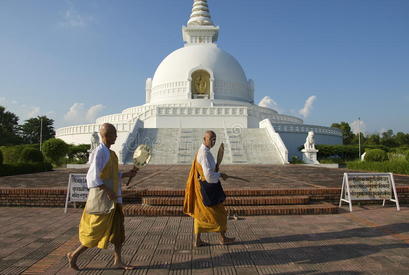 Lumbini, Nepal-September 17, 2013: Pilgrims pray at Lumbini Peace Pagoda royalty free stock photo