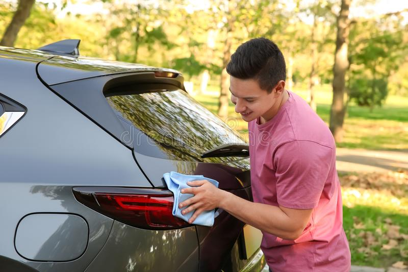Lumière arrière de lavage de voiture de jeune homme avec du chiffon images stock