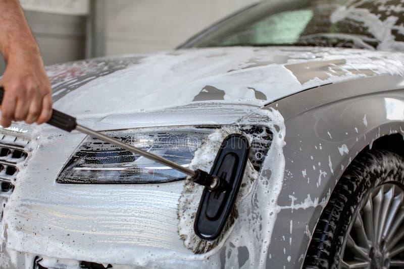 Lumière avant de la voiture argentée lavée dans la lave-auto de service d'individu, main d'homme photographie stock libre de droits