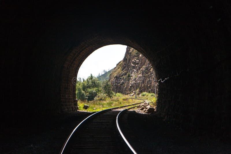 Lumière avec un paysage à l'extrémité d'un tunnel de chemin de fer en pierre avec les rails admirablement allumés dans les montag photos stock