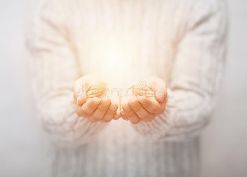 Lumière dans des mains image libre de droits