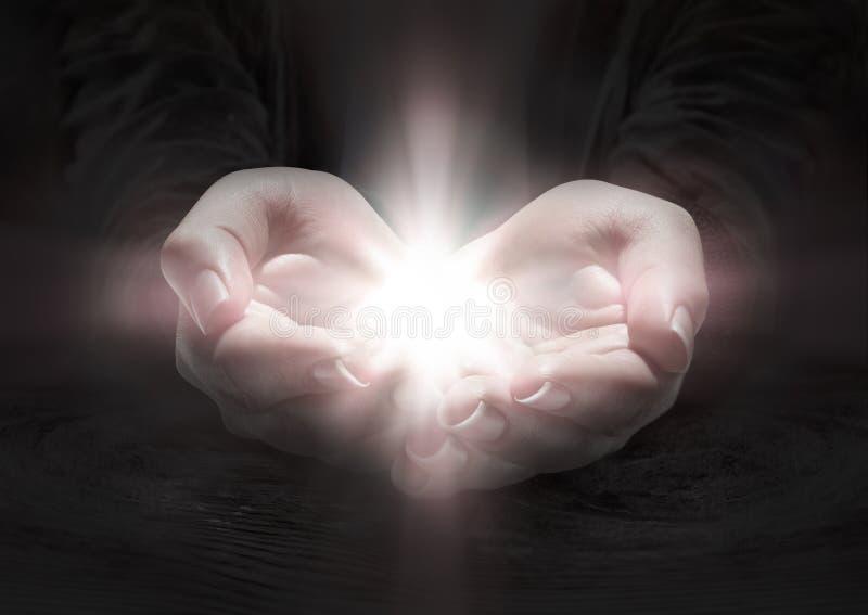 Lumière dans des mains - priez le crucifix images libres de droits