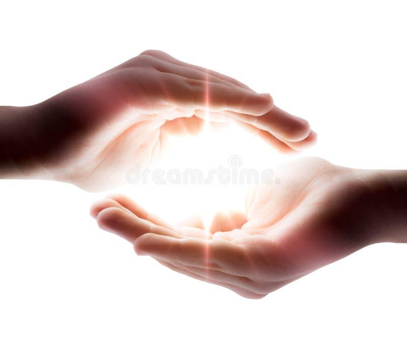Lumière dans les mains images stock