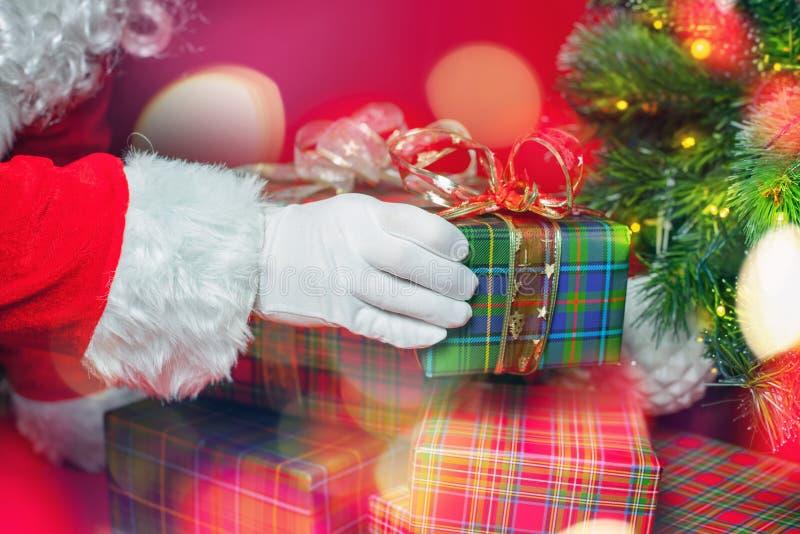 Lumière de Noël et inspiration avec Santa Claus mettant le boîte-cadeau photographie stock