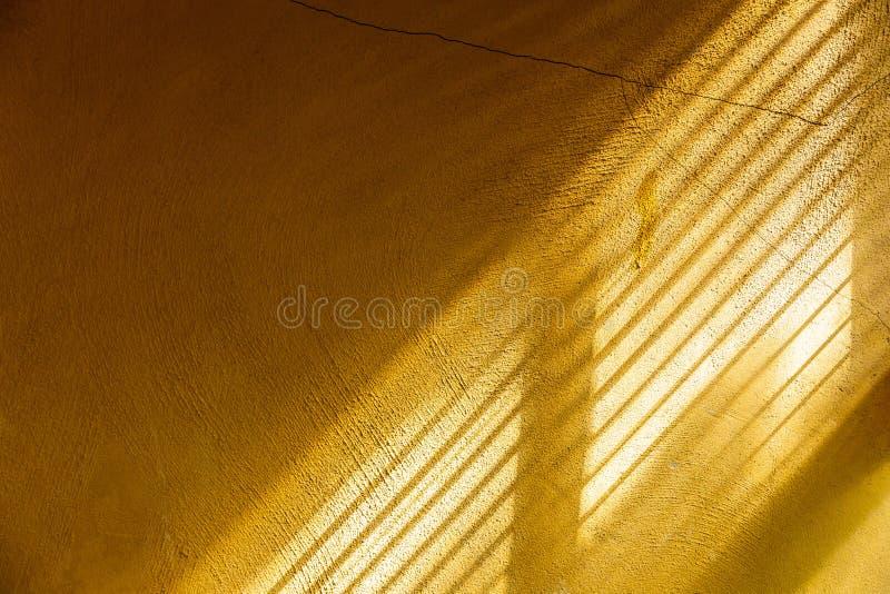 Lumière du soleil émouvante d'après-midi de mur jaune de ciment photographie stock