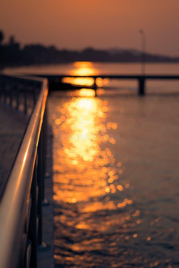 Lumière du soleil avec le bokeh sur l'eau à côté du rail en métal par la mer dans Sattahip, Thaïlande photo libre de droits
