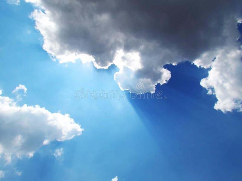 Lumière du soleil brillant par derrière les nuages contre le backgro de ciel bleu image libre de droits