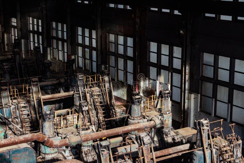 Lumière du soleil illuminant de vieilles machines de formation en acier à l'intérieur d'un entrepôt windowed photo stock