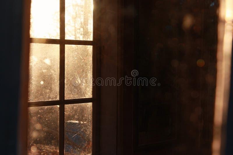 Lumière du soleil par la fenêtre dans une chambre noire images stock