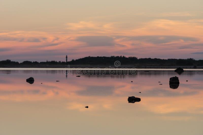 Lumière du soleil, phare et roches de soirée sur la réflexion de ciel de côte sur l'eau été de montagnes d'horizon de littoral de photographie stock libre de droits