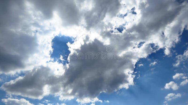 Lumière du soleil venant par les nuages blancs et gris de tempête de clairière, ciel bleu photos stock